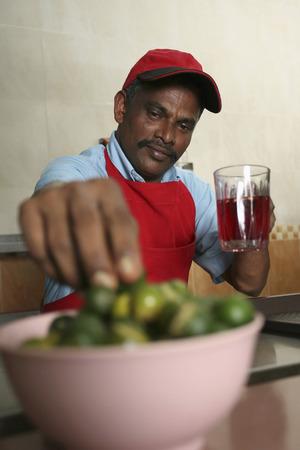 tomando refresco: Hombre que toma la cal que se a�ade en jarabe de bebida de lima