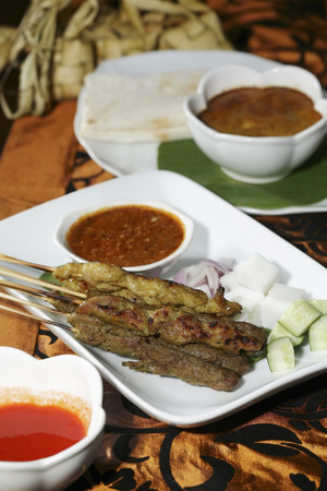 slivers: Satay with peanut gravy and slivers of onions and cucumbers, bread and curry in the background LANG_EVOIMAGES