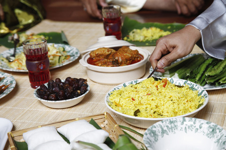 scooping: Man scooping nasi briyani, focus on food in the foreground