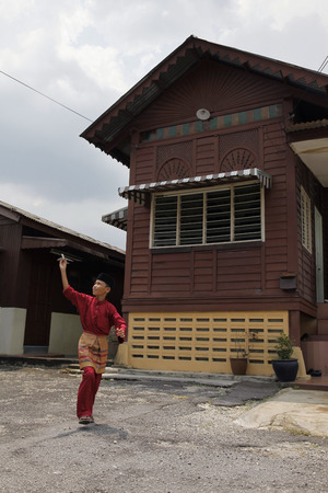 malay village: Boy playing with model airplane