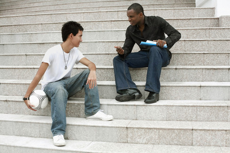 college life: Two men sitting and talking to each other on the staircase