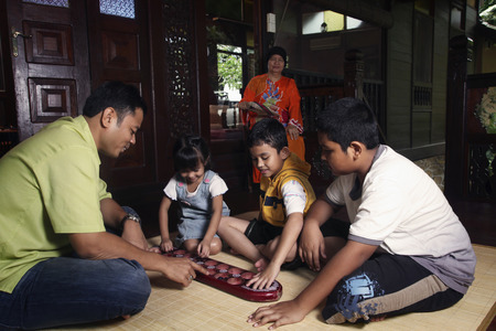 Man playing congkak with children, senior woman watching Foto de archivo