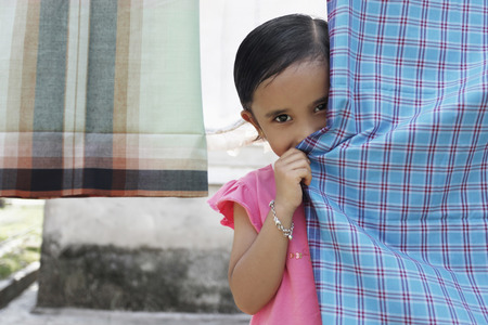 shy girl: Shy girl peeping from behind sarong on clothesline