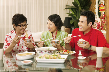 having lunch: Man and woman chatting and laughing while having lunch together with senior woman LANG_EVOIMAGES