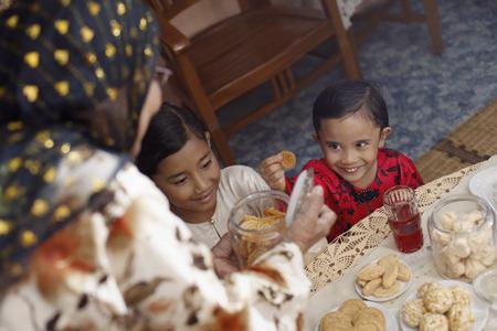 tomando refresco: Mujer mayor que ofrece a sus nietos galletas tradicionales LANG_EVOIMAGES