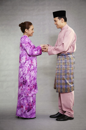 Man and woman in traditional clothing greeting each other