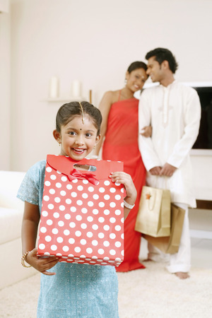 Girl posing with her gift, man and woman in the background LANG_EVOIMAGES