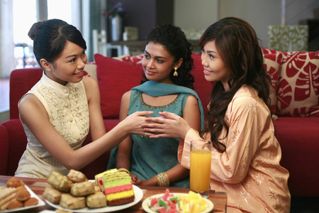 Women greeting each other, another woman watching 免版税图像