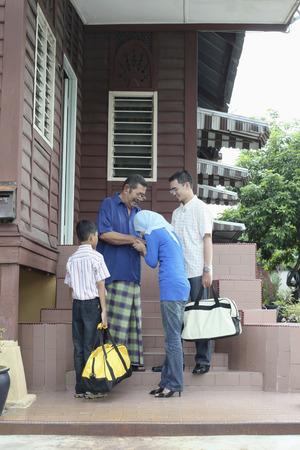 Woman greeting senior man, man and boy watching 免版税图像