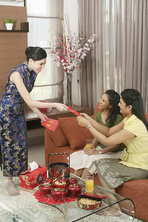 packets: Woman giving out red packets to her friends during Chinese New Year LANG_EVOIMAGES