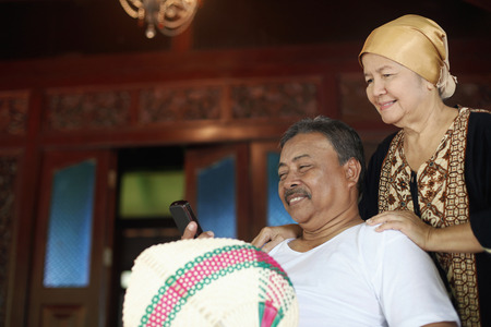 Senior man reading text message, senior woman standing behind him