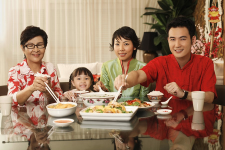 Couple and girl having lunch together with senior woman