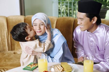 Boy kissing woman on the cheeks, man smiling Foto de archivo