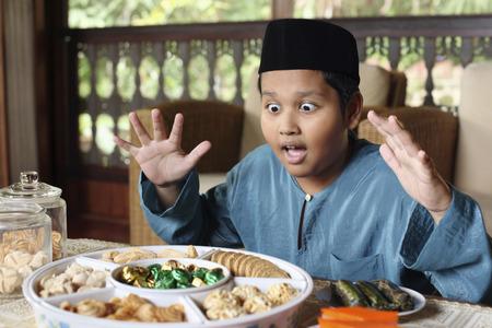 Junge, der die Vielzahl von Cookies mit Augen und Mund weit geöffnet