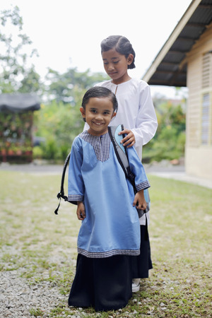 preadolescent: Girl helping her sister with backpack