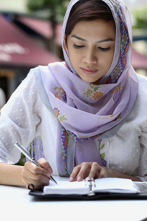 traditional clothing: Businesswoman in traditional clothing writing on an organizer