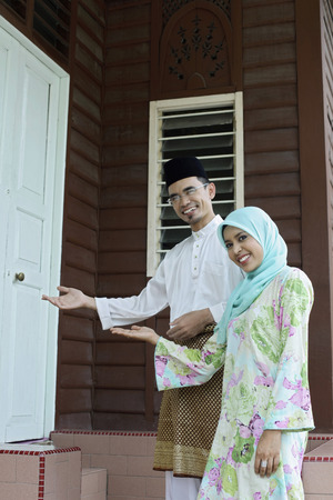 malay village: Man and woman standing with their arms outstretched