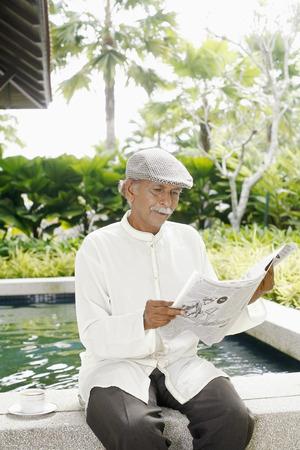 kurta: Senior man with beret reading newspaper