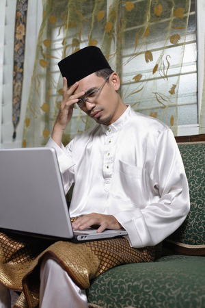 frowning: Man in traditional clothing frowning while using laptop