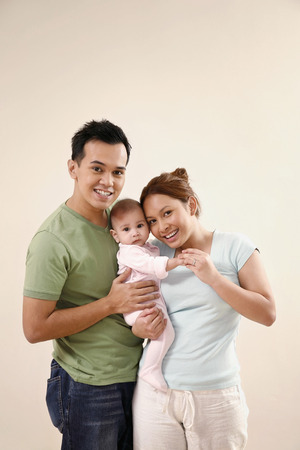 Man and woman posing with baby LANG_EVOIMAGES