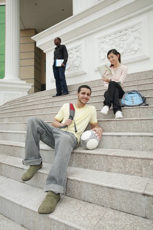 Man and woman sitting at the staircase of a college with man in standing in the background