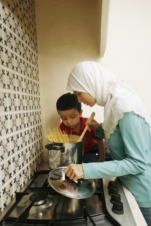 Boy watching woman prepare spaghetti