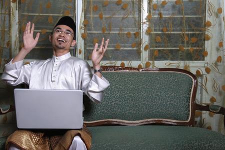 jubilating: Man in traditional clothing jubilating while using laptop