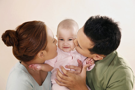 Man and woman kissing baby on the cheeks Standard-Bild