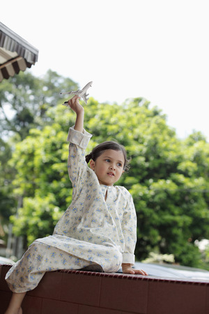 malay village: Girl playing with model airplane