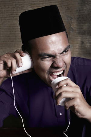 tin can telephone: Man shouting into tin can telephone