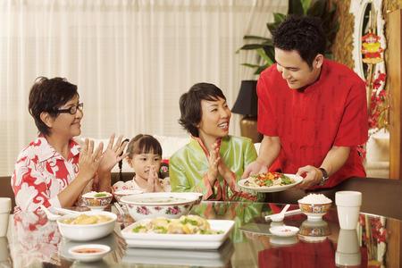 manos aplaudiendo: El hombre que sirve comida, mujer junto con la ni�a y la mujer mayor que aplauden las manos mientras se ve