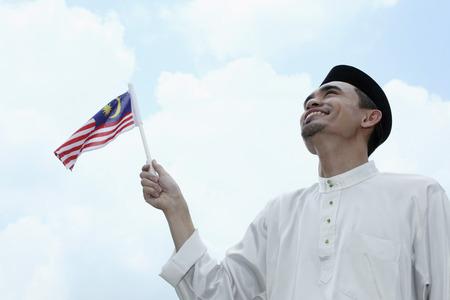 merdeka: Man smiling while waving flag LANG_EVOIMAGES