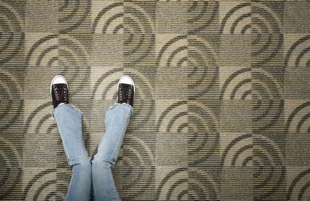 low section view: Woman with jeans and shoes sitting on a carpet floor LANG_EVOIMAGES