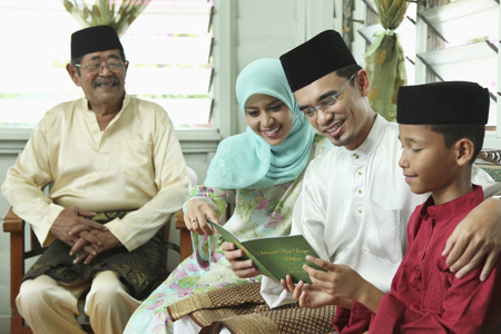 Boy reading greeting card with his parents, senior man watching Stock Photo