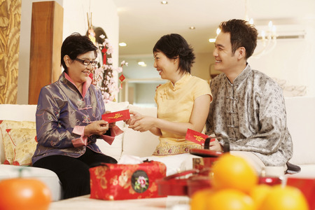 red packet: Man and woman getting red packet from senior woman