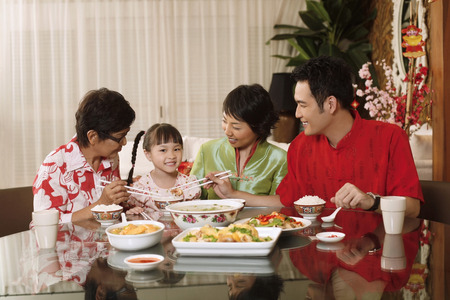 Couple and senior woman paying attention to girl while having lunch together LANG_EVOIMAGES