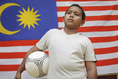 preadolescent: Boy holding soccer ball with Malaysian flag in the background