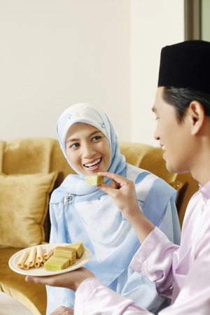 Man feeding woman cake during Hari Raya