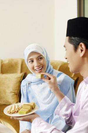 Mann Fütterung Frau Kuchen während Hari Raya