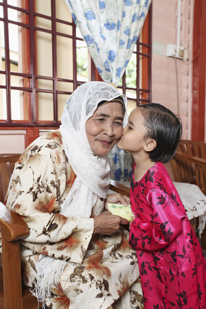 Senior woman giving green packet to granddaughter