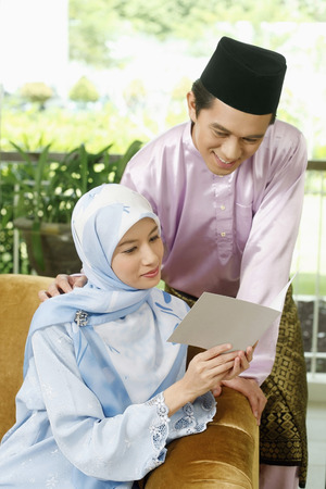 Man and woman reading greeting card