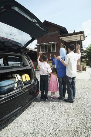 malay village: Kids and parents waving to senior man