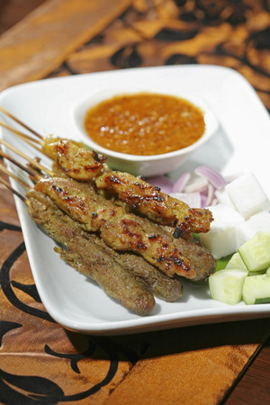 Satay with peanut gravy and slivers of onions and cucumbers