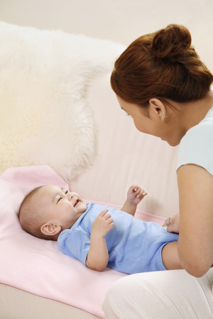 Woman playing with baby on the couch