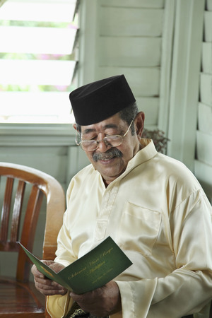 traditional clothing: Senior man in traditional clothing smiling while reading greeting card LANG_EVOIMAGES