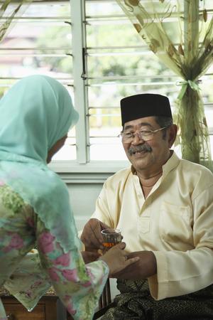 tomando refresco: Mujer sirviendo hombre mayor un vaso de jarabe de rosa