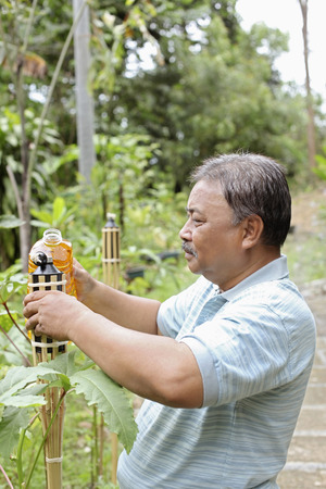 malay village: Senior man pouring oil into bamboo torch