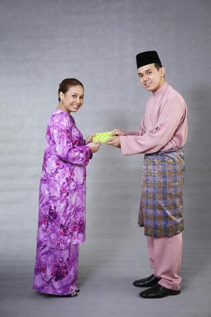 Receiving: Woman receiving green packet from man