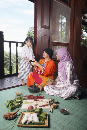 Girl passing a bowl of rice to senior woman, young woman smiling while watching