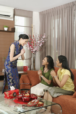 three people only: Woman greeting her friends during Chinese New Year